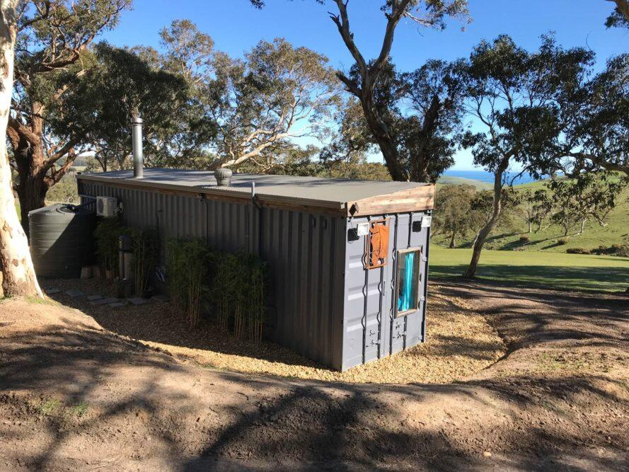black corrugated metal tiny home facing hilly landscape