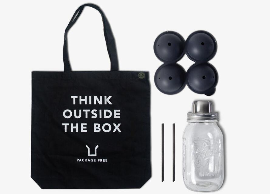 """A black tote bag reading """"Think outside the box,"""" a set of four ball ice molds, two metal straws and a mason jar shaker."""