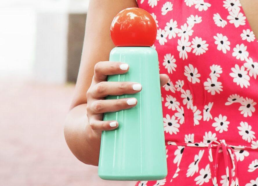 A hand holding a retro cyan and red water bottle.