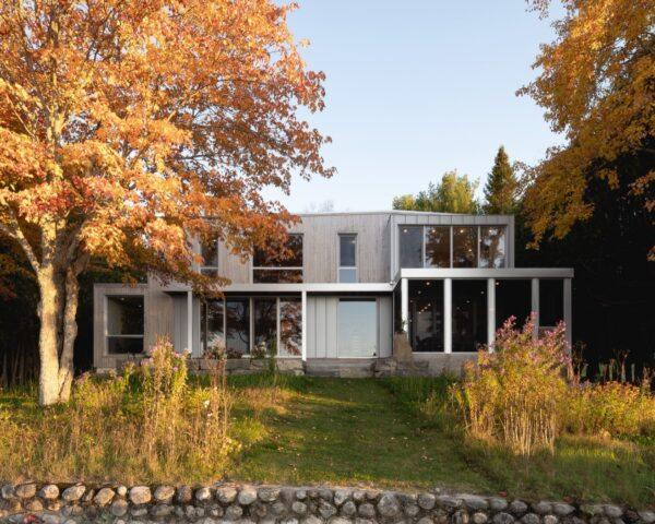 A two-story home with a gray facade broken up by large windows. The home is flanked on both sides with trees in fall colors.