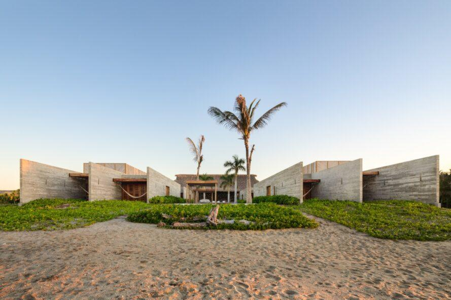 The exterior of a beach house, with sand, greenery and palm trees in the front yard. The home is comprised of a U-shaped, off-white wood volume.