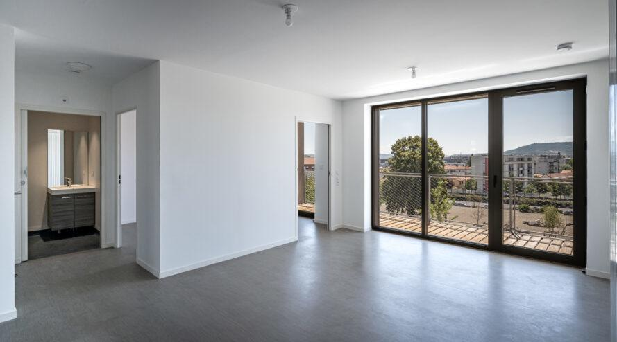 large white room with sliding glass doors leading to a balcony