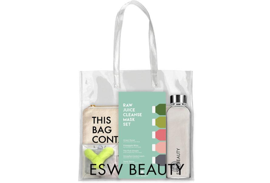 """A clear tote bag reading """"ESW Beauty"""" with a water bottle, headband, canvas bag and a pack of sheet masks inside."""