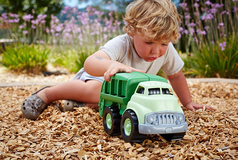 kid playing with green recycling truck toy