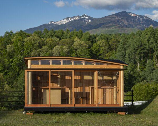 a compact timber home with a curved roof set against a green background with mountains.
