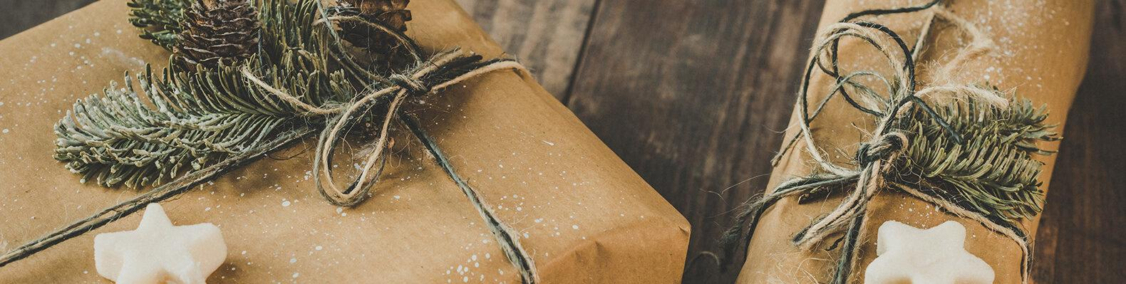 Brown paper packages tied up with string and decorated with white star shapes, pine needles and pinecones.