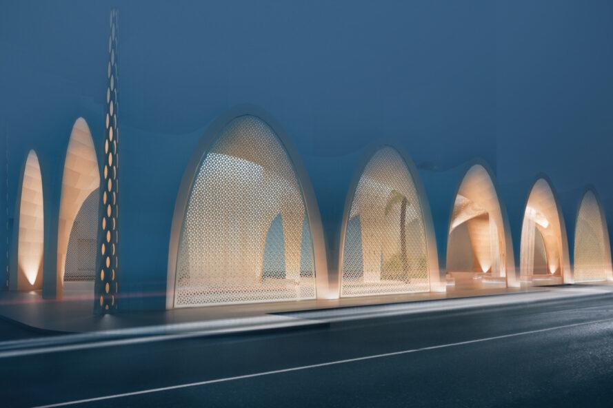 rendering of dune-like building lit from within at night