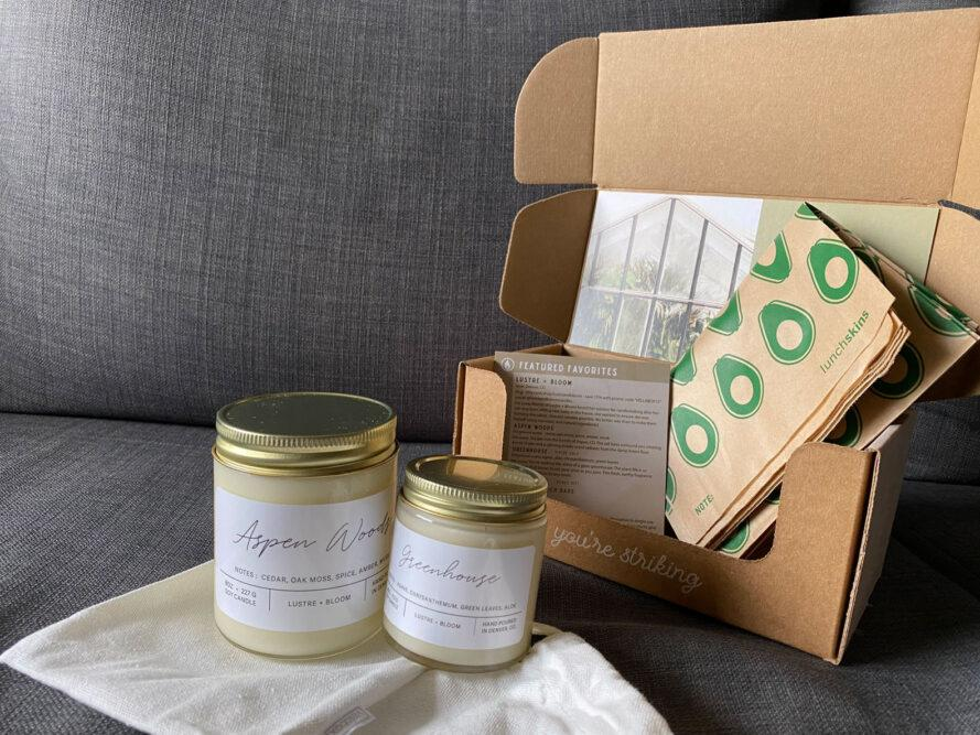 two candles and paper sandwich bags inside a cardboard box
