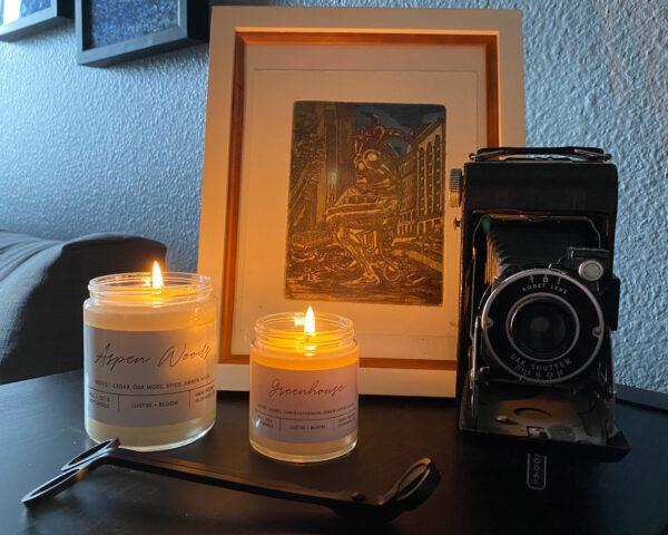 two lit candles near a camera and a drawing