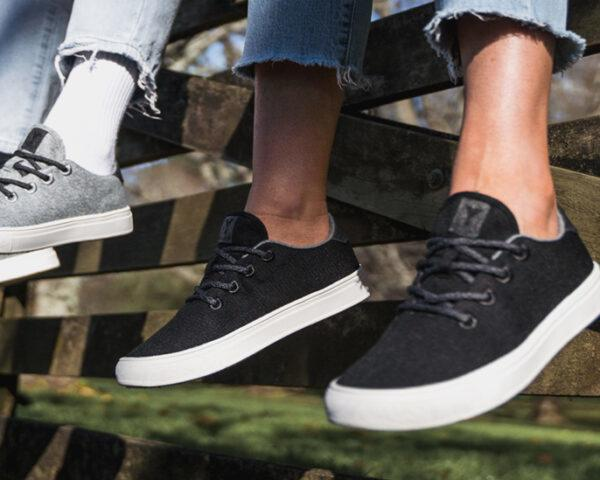one person in black sneakers and one person in gray sneakers both sitting on a fence
