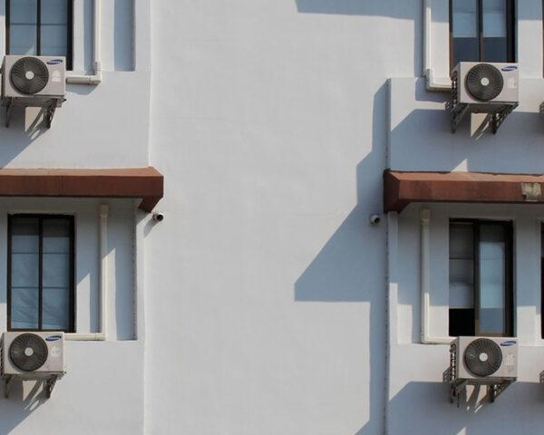 air conditioners on windows of white building