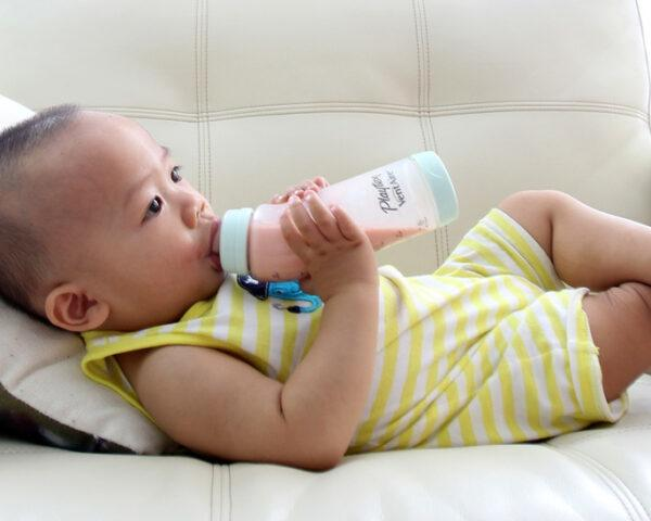 baby drinking from plastic bottle