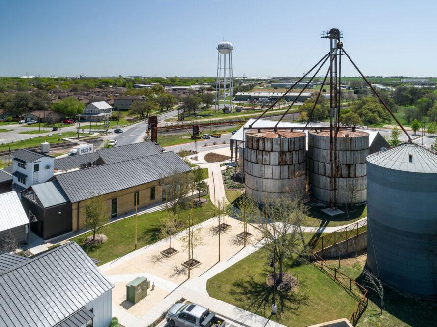 aerial view of property with gabled buildings and rusty silos
