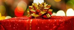 a close-up of a red-wrapped gift with a gold bow.