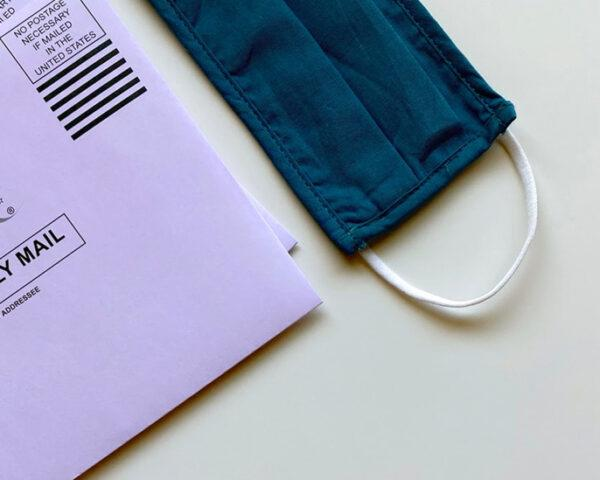 ballot mail envelope next to blue face mask