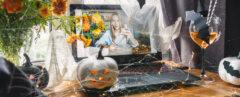 person video-chatting with someone with pumpkins and flowers on table
