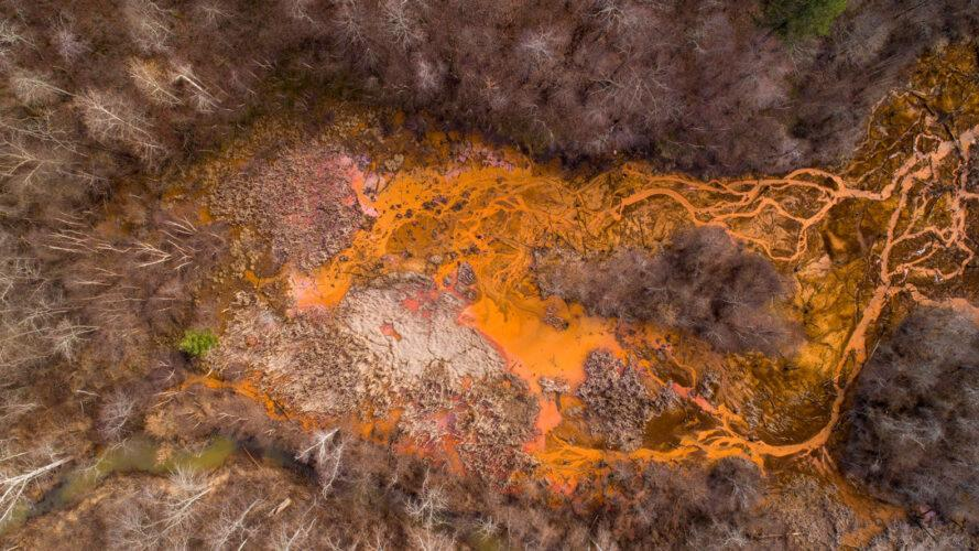 aerial view of orange streams in a forest