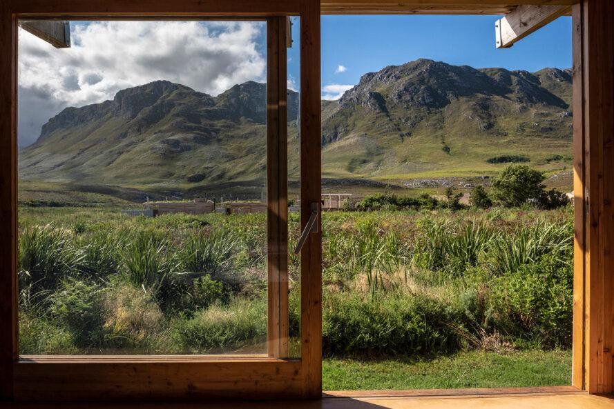 wood-framed sliding glass door opening to mountain views