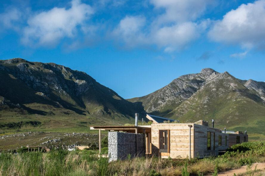 stone and wood cabins with mountains in background