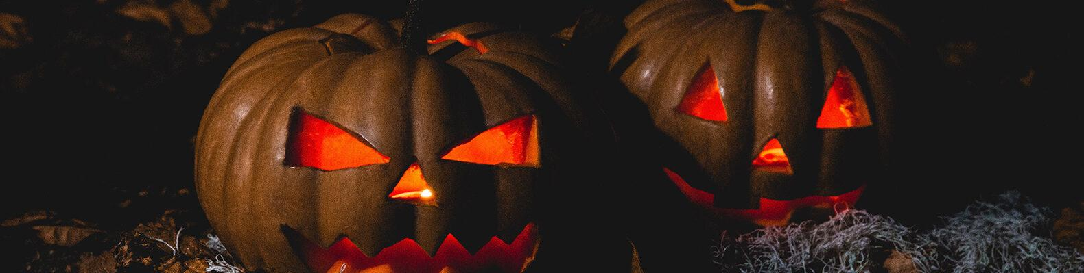 two jack-o-lanterns lit up in a dark setting