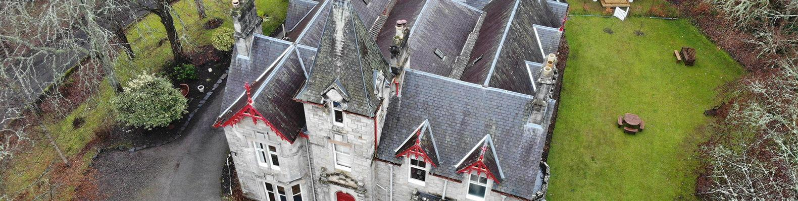 An aerial photo of a 19th century building with grey stone and red accents.