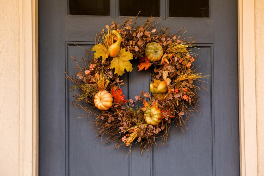 a door wreath with small pumpkins and fall leaves