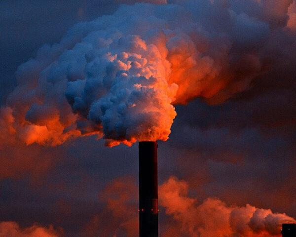 a blue and red photo of a smoke stack emitting pollution