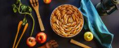 apple pie on black background with wood spoons and apples