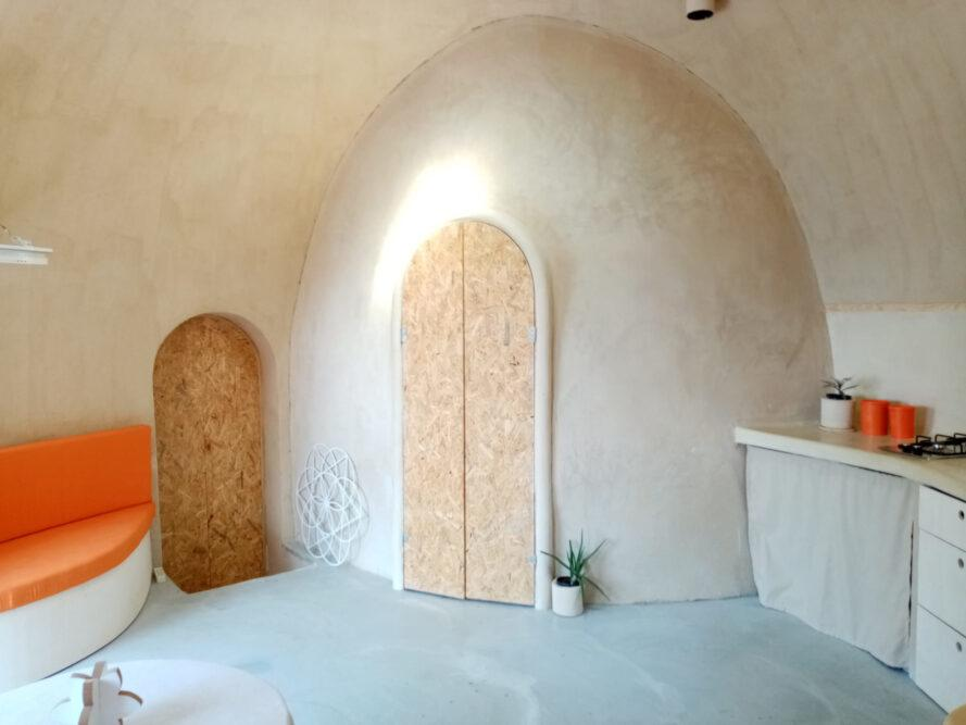 wood door on a curved wall inside dome home