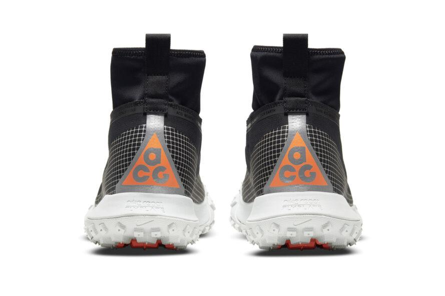 The back of a white and black pair of Nike ACG Air Mountain Fly Gore-Tex shoes, with orange highlights.