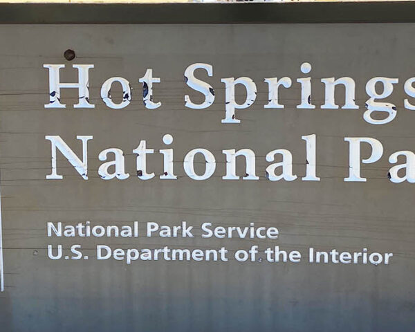 A Hot Springs National Park sign in front of a yellow building.