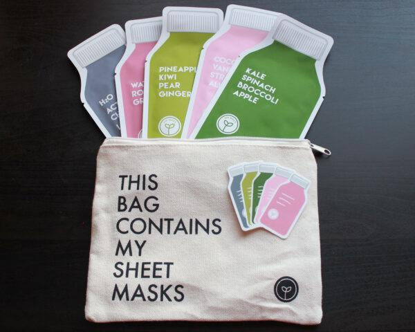 A canvas pouch full of five sheet masks in black, dark pink, light green, light pink and dark green. A sticker sits on top of the bag.
