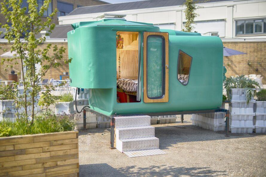 green tiny home with door open