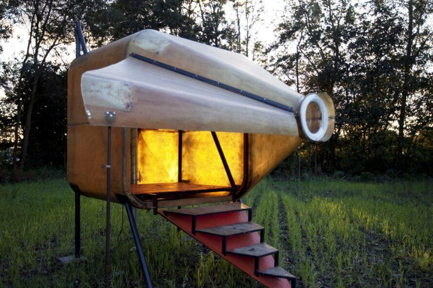 spaceship-shaped tiny home on grassy lot