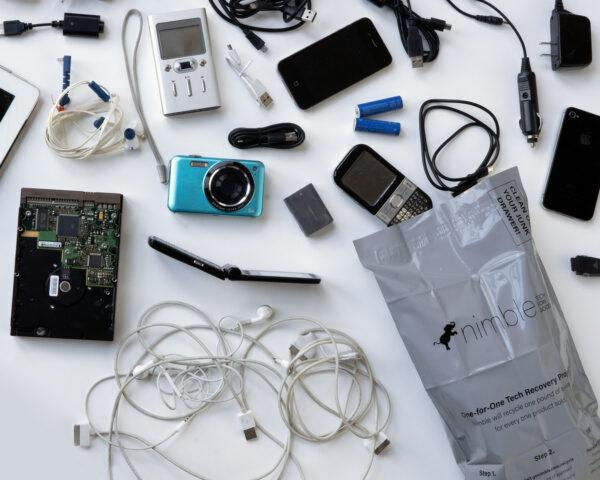 old tech gadgets spilling from recyclable bag