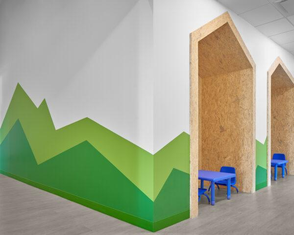 white room with green mountains painted on the wall