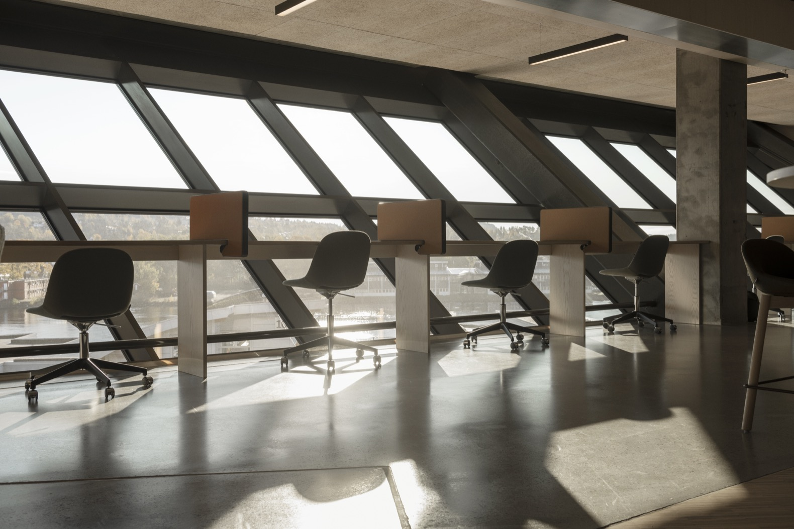 small chairs and desks by wall of glass