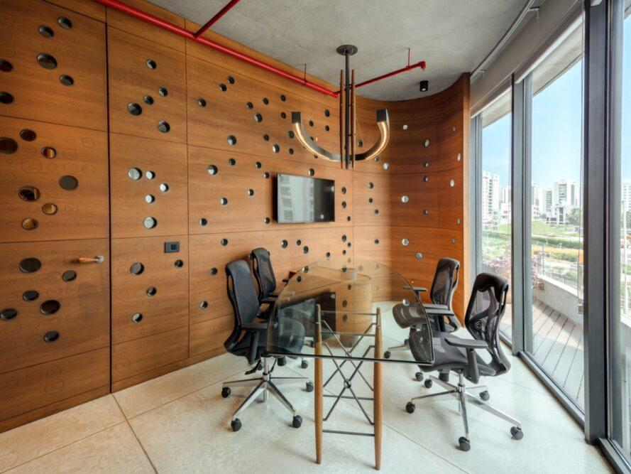 glass desk and meeting chairs near wood wall and glass wall