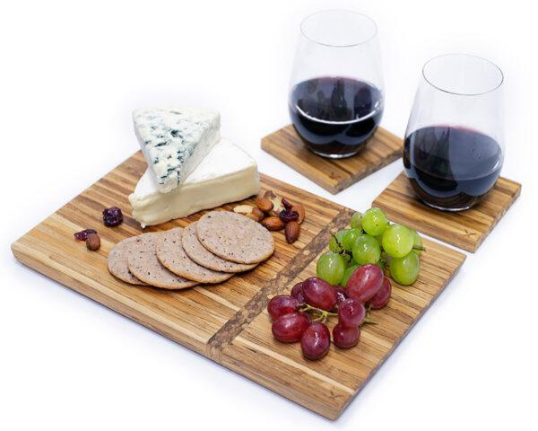 A cheese board accompanied by two glasses of red wine.