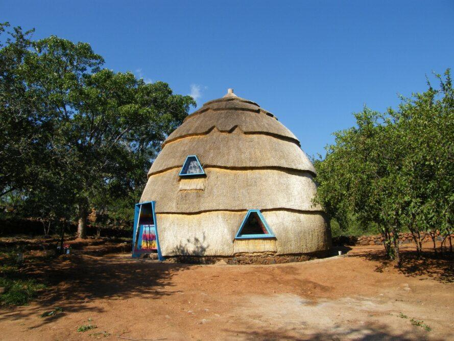 A thatched dome with blue frames for the door and windows.