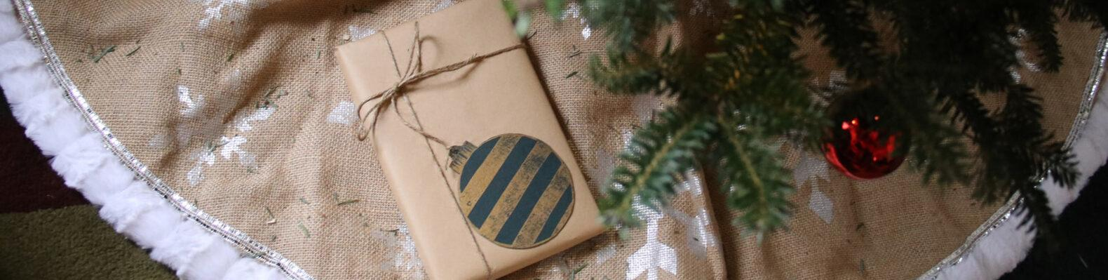 gift wrapped in brown paper placed under a Christmas tree