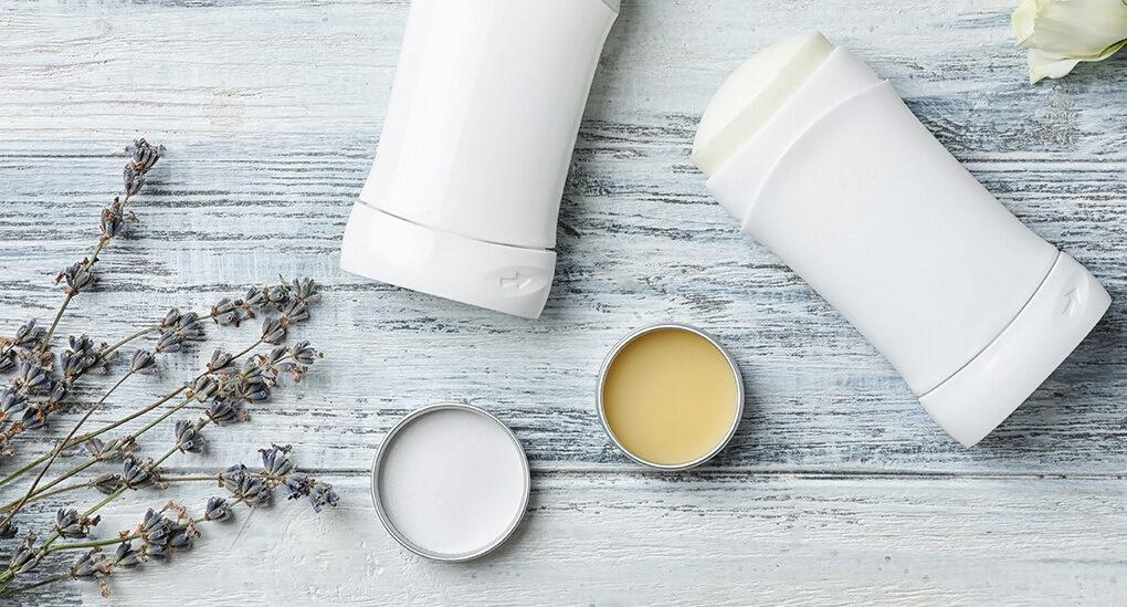 natural deodorant in metal tins next to antiperspirant in plastic containers