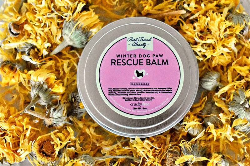 paw balm in tin can on bed of flowers