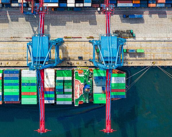 A bird's-eye view of a shipping area with cranes loading containers onto ships.