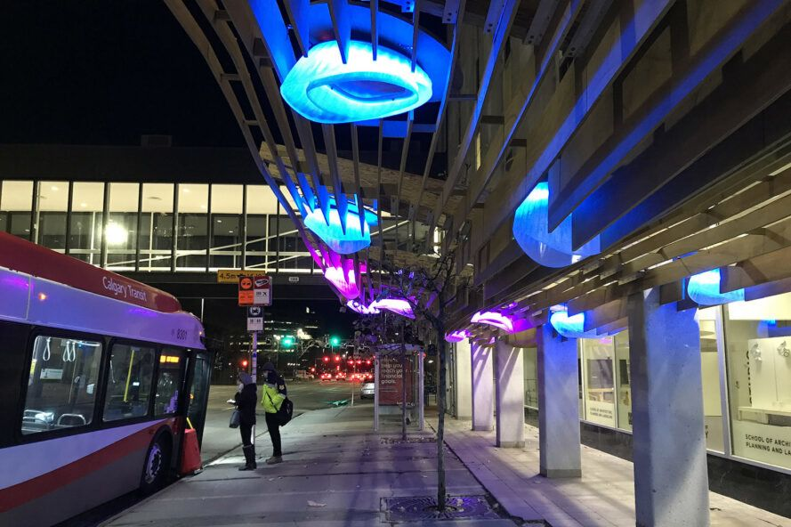 A wood canopy with blue and purple lights.