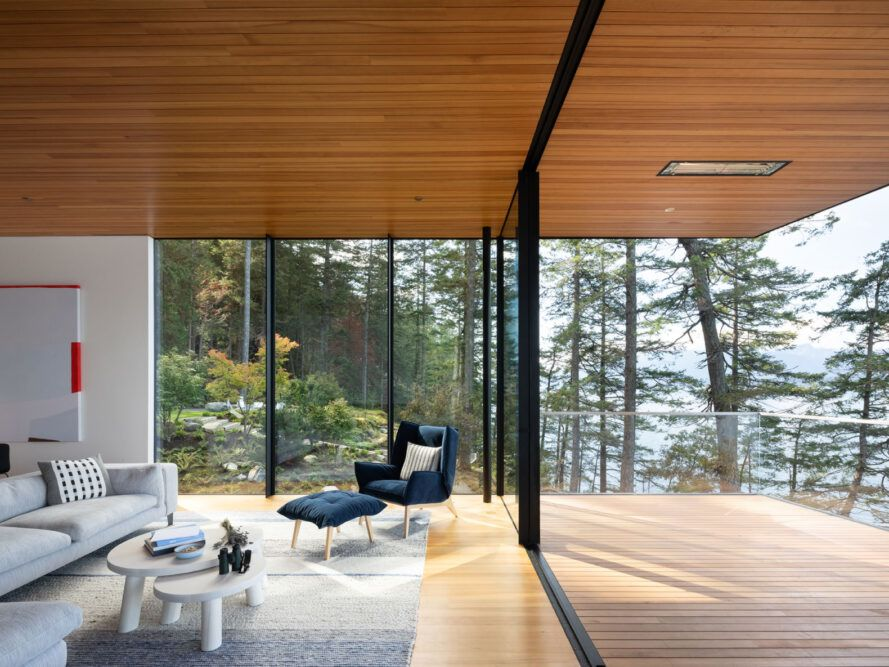 blue chair and foot rest near two glass walls leading to wood balcony
