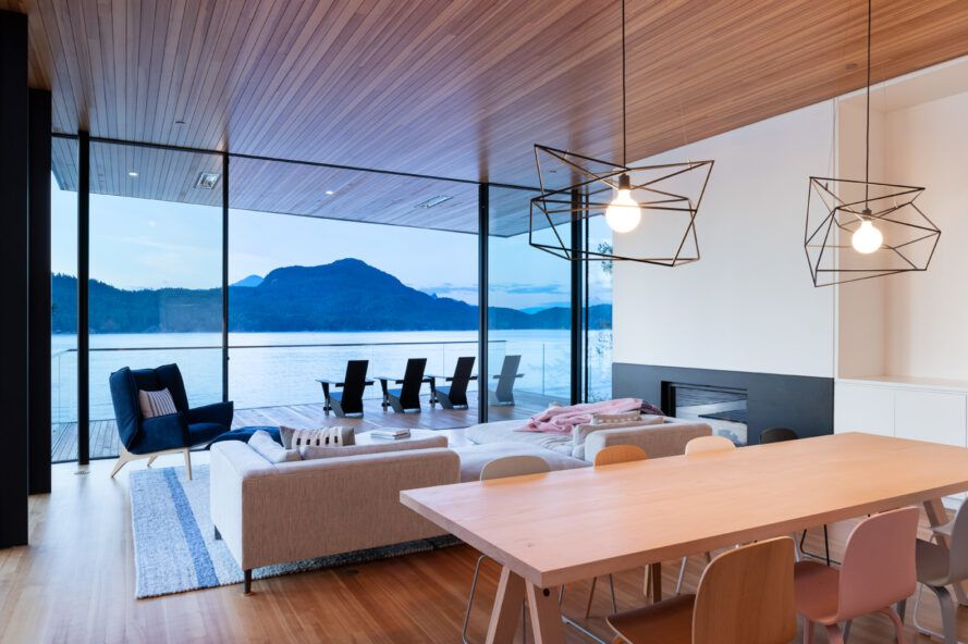 wood dining table near white sofa in room with wood ceiling and glass wall