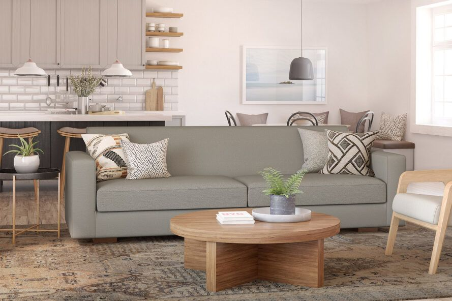 A gray sofa and round wood coffee table in a living room.
