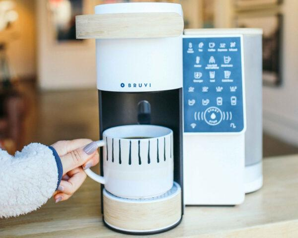 person grabbing mug of hot coffee from under a white coffee machine