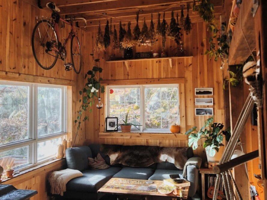 The interior living room of a small cabin, complete with an L-shaped sofa, windows and decorations such as plants and pictures.